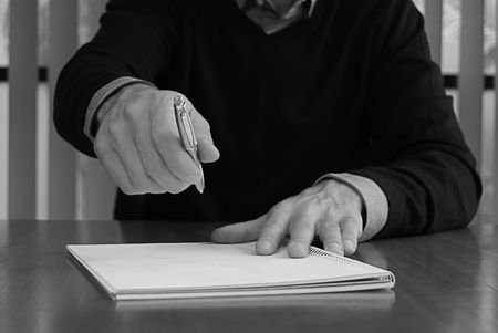 a black and white shot of a businessman passing a pen and notepad, photo
