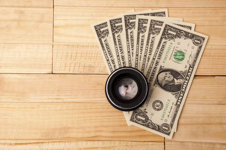 exclusive photo: Photo lens with money on light wooden background. Buying expensive photographic equipment.