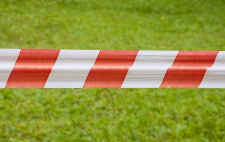 Red and white warning tape on green grass background in summer Stock Photo