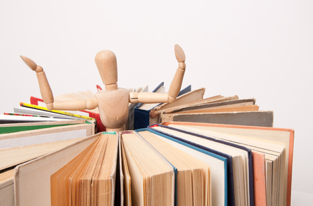 relevant: Figure of the toy wood man stand inside the circle made of books. Search for relevant and necessary information in a large number of sources during studies or work.