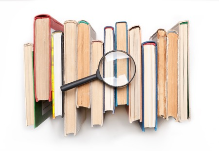 Stack of hardback books with magnifying glass isilated on white background, top view. Search for relevant and necessary information in a large number of sources during studies or work. Stock Photo