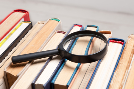 relevant: Stack of old hardback books with magnifying glass. Search for relevant and necessary information in a large number of sources during studies or work.