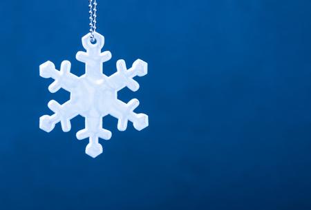 Reflector blanco lindo de la seguridad bajo la forma de copos de nieve en fondo azul. Equipo necesario para los peatones para caminar durante las condiciones de oscuridad