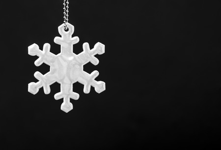 Black and white photo of safety reflector in the form of snowflakes. Necessary equipment to pedestrians for walks during dark conditions Foto de archivo