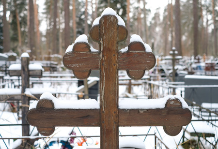 Beautiful wooden cross of traditional shape and artificial flowers on the grave of the Orthodox cemetery in winter.