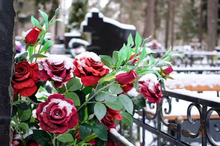 Artificial flowers bouquet of roses on the grave in the winter. Cemetery decorations. Selective focus