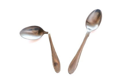 Two metal teaspoons - broken in half and serviceable on a white background. The concept of individuality in society and the family. Reklamní fotografie