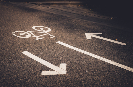 Bicycle sign and arrows on the road. White painted bike on asphalt. Ecological green urban transport