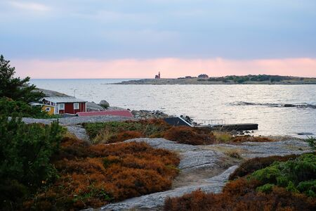 Beautiful scandinavian landscape with stones and moss. Traditional red swedish houses. Sea at sunset, the lighthouse on the island. Travel to Europe. Stockfoto