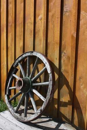 Abandoned wagon wheel against a wooden wall Stock Photo - 9272466