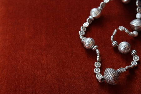 bead: Silver bead necklace on an orange brown background