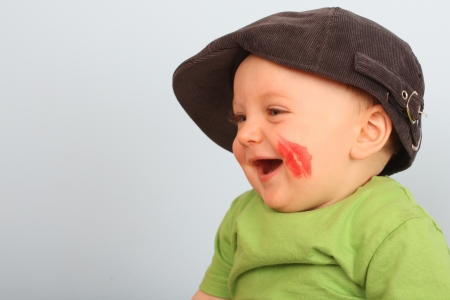 cheek to cheek: Beautiful baby boy with red lips on his cheek