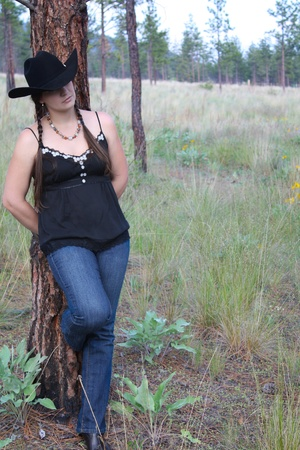 Brunette female in the field wearing a black cowboy hat photo