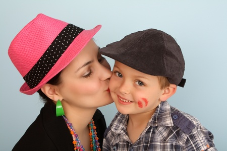 accesories: Brunette mother kissing her son on his cheek Stock Photo