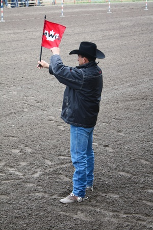 MERRITT; B.C. CANADA - MAY 15: Unidentified cowboy and marshall holding up a red flag at Nicola Valley Rodeo on May 15; 2011 in Merritt; British Columbia; Canada