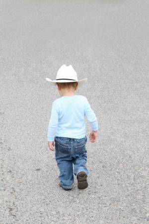 Toddler cowboy walking down the street captured back photo