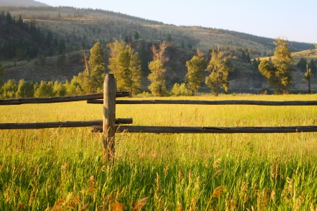 Farm fence and green fields at sunset photo