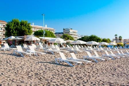 Sunbeds and umbrellas at beach of Pineda De Mar  Costa Brava  Spain Editorial
