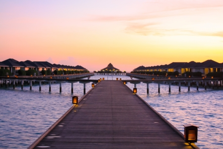 Tropical beach water bungalow at softly beautiful violet sunset