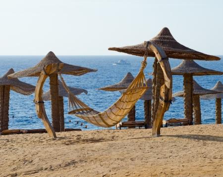 Hammock on the beach and boat far into the sea  Stock Photo