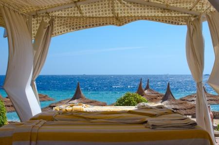 Beach spa gazebo with white canopy, blue sea background