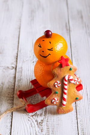 Fruit snowman with Christmas cookies on a red sled photo