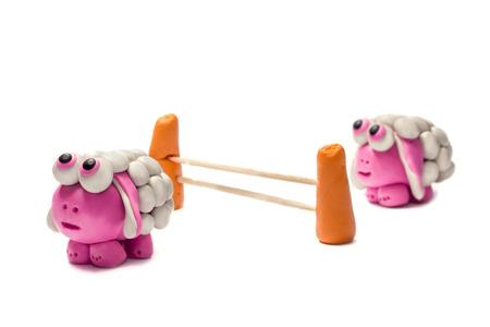 salto de valla: Dos peque�as ovejas saltando plastilina sobre una cerca. Fondo blanco.