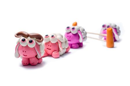 salto de valla: Poco ovejas saltando plastilina sobre una cerca. Fondo blanco.