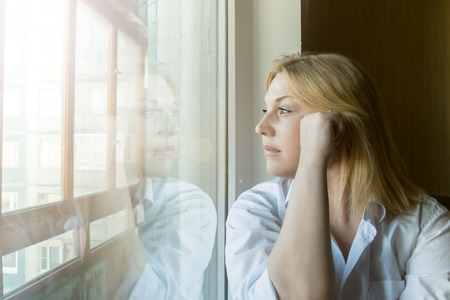lost in thought: The woman lost in thought looking out the window. Sunny morning. Stock Photo