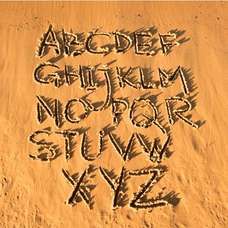 latin alphabet: Latin alphabet handwriting on the sand. Sunset on the beach. Stock Photo