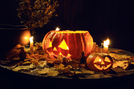 pumpkin face: The composition of the candles, pumpkins and maple leaves. Decor for Halloween.