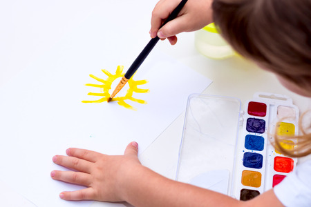 bonny: Childrens drawing water color on paper. The child draws the sun.