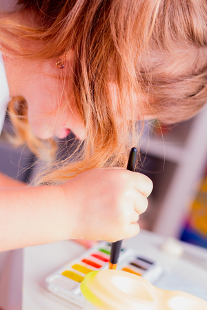 selective focus: Little beautiful girl draws paints. Selective focus.
