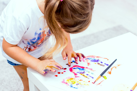 bonny: Little beautiful girl draws paints, her hands are covered with watercolor. Selective focus. Focus on hands.