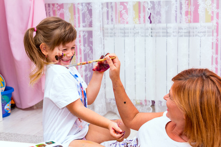 bonny: Mom draws paints on a T-shirt daughter lying on the floor. Family fun. Stock Photo