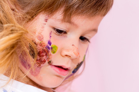 bonny: Portrait of a pretty little girl. Her face and hands painted with watercolors.