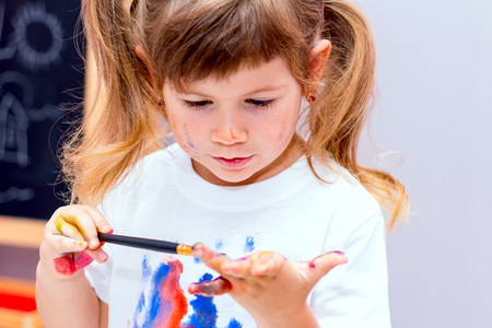 bonny: Little beautiful girl draws paints. Her face and hands are covered with watercolor.