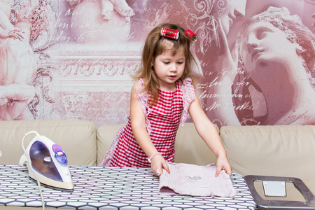 homemaker: Little girl in curlers irons clothes Stock Photo