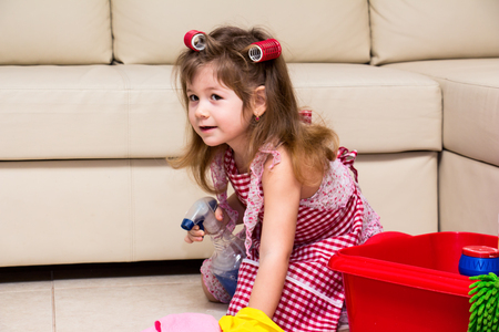 homemaker: Little girl in curlers cleaning the floor