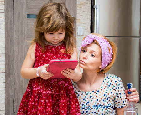 homemaker: Little girl and her mother looking at the screen of the gadget. The concept of modern life.