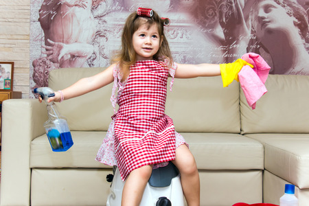 hair curlers: Little girl in hair curlers sits on a vacuum cleaner.