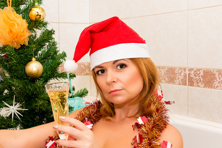 hat nude: Beautiful woman sits near Christmas tree with glass of champagne. Stock Photo