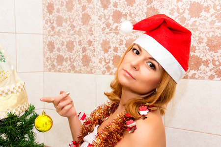 hat nude: Beautiful woman decorates a Christmas tree in the bathroom.