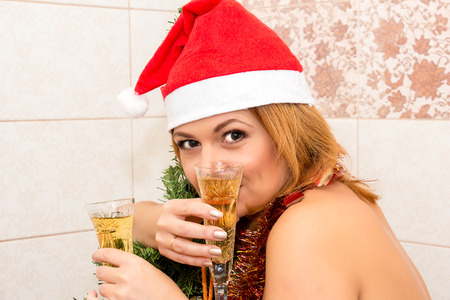 nude christmas: Beautiful woman drinking champagne in the bathroom. Christmas decorations. Stock Photo