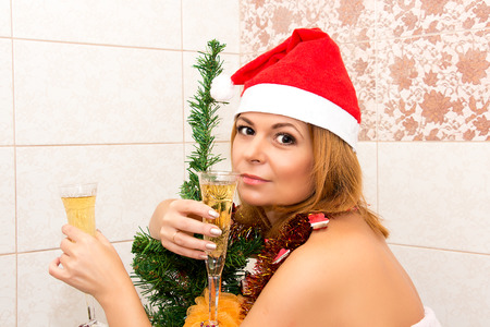 hat nude: Beautiful woman drinking champagne in the bathroom. Christmas decorations. Stock Photo