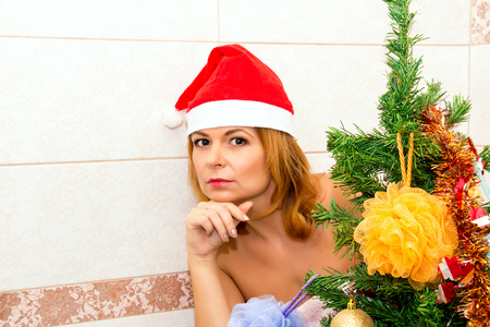 hat nude: Portrait of a beautiful woman in Santa hat near Christmas tree.