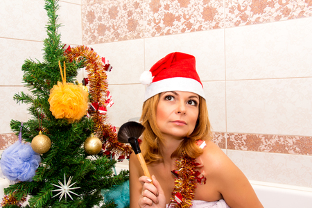 glamour nude: Beautiful woman holding makeup brush near Christmas tree in the bathroom.