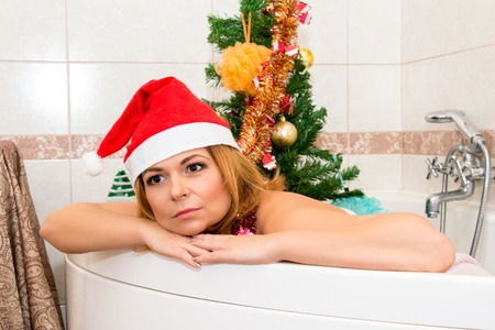 hat nude: Beautiful woman in Santa hat lying in the bath. Christmas decorations.