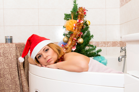 nude christmas: Beautiful woman in Santa hat lying in the bath. Christmas decorations.