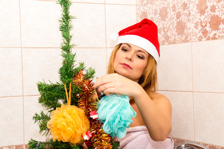 nude christmas: Beautiful woman decorates a Christmas tree in the bathroom.